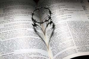 Auf einer aufgeschlagenen Bibel liegt ein Stacheldrahtkranz, dessen Schatten eine Herzform bildet.